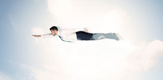 Business man flying like a superhero in clouds on the sky Stock Photo