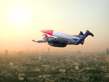 Business man flying with rocket over skyscraper scene Stock Images