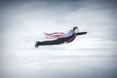 Business man flying with USA flag as a cape Stock Photography