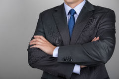Business man with folded hands. Against gray background. Copy space Stock Photos