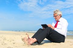 Business man working on tablet at the beach royalty free stock photos