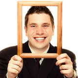 Business man framing his face with wood frame Royalty Free Stock Image
