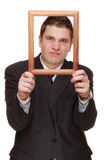Business man framing his face with wood frame Royalty Free Stock Images