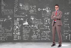 Business man in front of a wall with big plans Stock Photography
