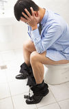 Business man with frustrated expression sitting toilet seat. Painful to holding head Royalty Free Stock Image