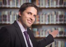 Business man gesturing towards blurry bookshelf Royalty Free Stock Images