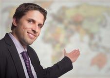 Business man gesturing towards blurry map Royalty Free Stock Photos