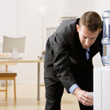 Business man gets water from water cooler stock photos