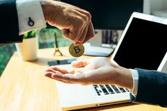 Business man give his a bitcoin to other. Business man in the office Stock Photos