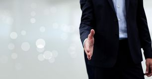 Business man giving hand against white blurred background Stock Photo