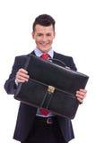 Business man giving his briefcase Stock Photos