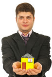 Business man giving miniature house Stock Photos