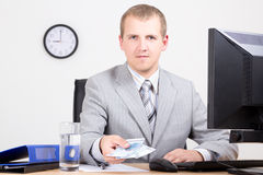 Business man giving money in bright office Stock Images