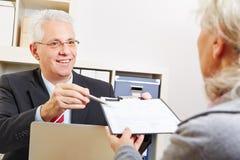 Business man giving senior woman Stock Image