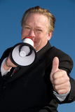 Business man giving thumbs up. Friendly business man holding a megaphone and giving the thumbs up sign. Blue sky is the background Royalty Free Stock Image