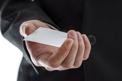 Business man giving a visit card. Closeup of a business man giving a blank visit card Royalty Free Stock Images