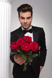 Business man giving you a bouquet of red roses Stock Images