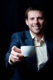 Business man giving you a coffee cup. Smiling business man giving you a coffee cup, focus on a cup Stock Photo