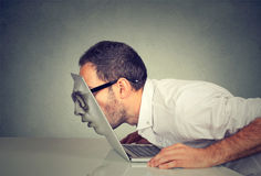 Business man in glasses passing his head through a laptop screen stock photography