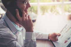 Business man with glasses using black mobile phone. stock photo