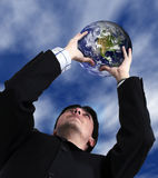 Business man with globe with sky in the background Royalty Free Stock Image