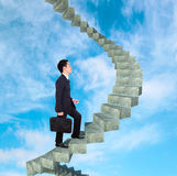 Business man going upstairs in a curved staircase to success  Royalty Free Stock Photography
