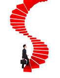 Business man going upstairs in a curved staircase to success Royalty Free Stock Photo