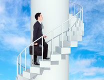 Business man going upstairs in a curved staircase to success wit Royalty Free Stock Images