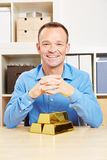 Business man with gold bars in office Stock Photos