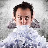 Business man with a great heap of crumpled papers. Royalty Free Stock Image