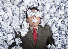 Business man with a great heap of crumpled papers. Swimming in paper ocean concept Royalty Free Stock Images