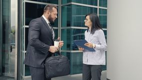 Business man greeting a young woman at the entrance to the office building.  stock video