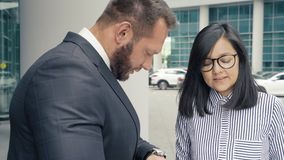 Business man greeting a young woman at the entrance to the office building.  stock footage