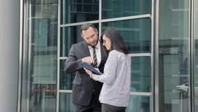 Business man greeting a young woman at the entrance to the office building.  stock video footage