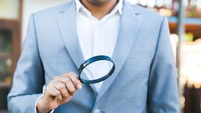 A business man holding a magnifying glass. royalty free stock image