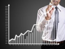 Business man hand drawing a graph stock images