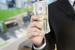 Business man hand and giving money with blur background of IT sh. Business man hand and giving money  with blur background of IT shopping mall Royalty Free Stock Image