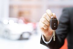 Business man hand holding car key front with car in showroom royalty free stock photography