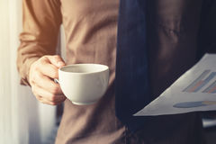 Business man hand holding coffee cup and paper sheet at window i Stock Photo