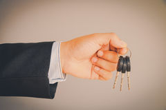 Business man hand holding keys Royalty Free Stock Images