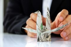 Business man hand holding origami paper cranes