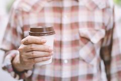 Business man hand holding paper cup of take away drinking coffee  on natural morning sunlight. Space Place for your text or logo royalty free stock photo