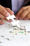 Missing puzzle piece, money concept. Business man hand holding a puzzle piece, money concept Royalty Free Stock Photos