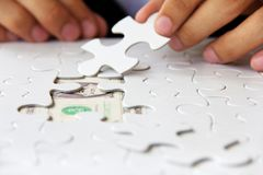 Hand holding a puzzle piece, money concept Stock Images