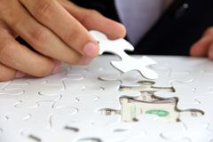 hand holding a puzzle piece, money concept Stock Photography