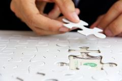 Hand holding a puzzle piece, money concept Royalty Free Stock Photo