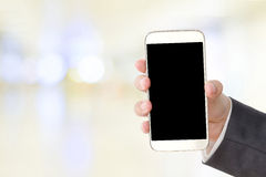 Business man hand holding smart phone over blur abstract backgro Stock Photo
