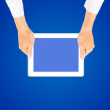 Business man hand holding tablet PC. On blue background Stock Photo