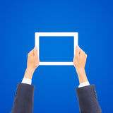 Business man hand holding tablet PC. On blue background Royalty Free Stock Photos