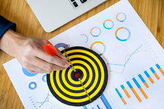 Business Man hand holding a target with darts hitting the center. Business Man hand holding a target Royalty Free Stock Photography